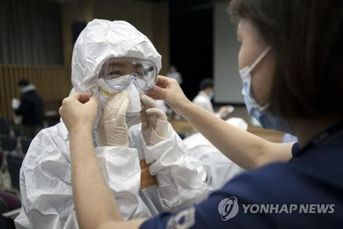 Medical staffers at Seoul Medical Center in Seoul practice wearing protective gear on Feb. 27, 2020, ahead of the center's upcoming change from being a general hospital to a COVID-19-only one, in this photo provided by the clinic.