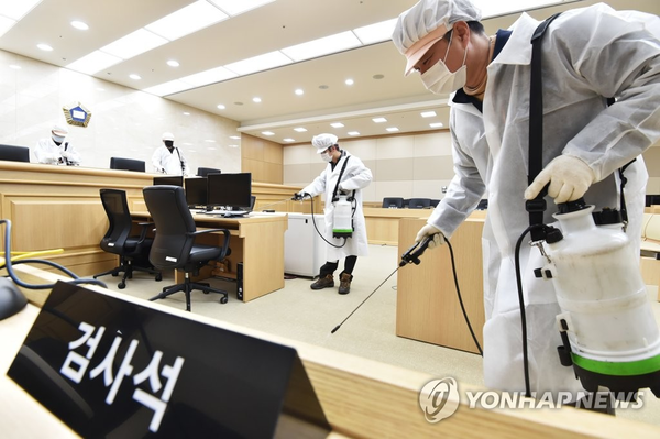 Health workers disinfect a courtroom in Suwon, south of Seoul, on March 1, 2020, as South Korea beefs up its efforts to prevent the spread of the novel coronavirus. (Yonhap)