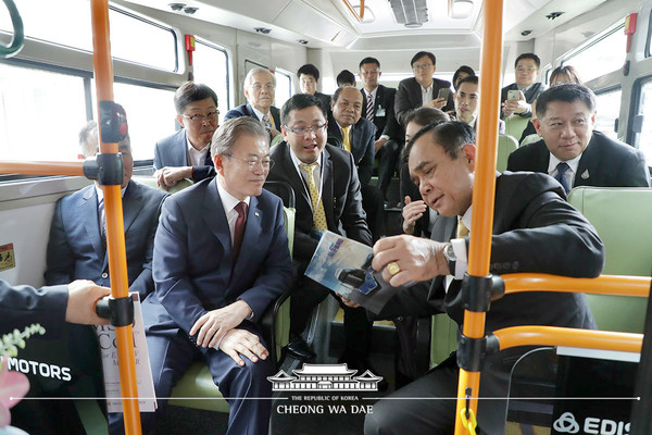 President Moon Jae-in of Korea (left, foreground) and Prime Minister Prayut Chan-o-cha of Thailand (right, foreground) discuss tourist attractions in each other's country with a view to promoting tourist exchanges between the two countries. Leaders of the two countries are onboard one of the deluxe buses of Edison Motors.