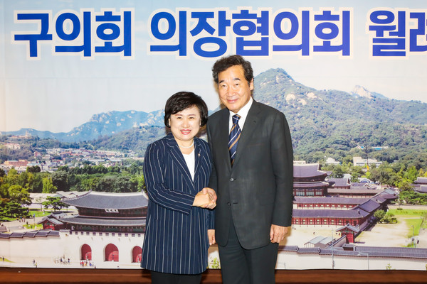 Chairperson Choi Yoonnam of the Nowon District Council in Seoul (left) shakes hands with Chairman Lee Nak-yon of the ruling Democratic Party at a Seoul City Council leaders meeting in Seoul in August 2020.