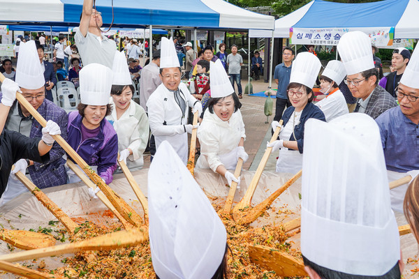 "Chairperson Choi (fifth from left, front row) makes an extra-large size of Bibimbap (rice mixed with vegetables and meat) on the occasion of the 12th ""Citizen of the World"" (or ""Together Day"") commemoration meeting in Nowon-gu, Seoul in 2019."