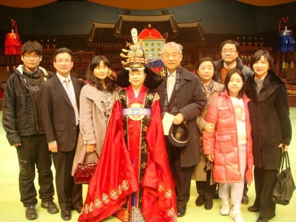Lady Novelist Han Malsook (in traditional Korean royal costume) and her late husband (noted Korean Gayageum Specialist Hwang Byung-ki (fourth and fifth from left, respectively) pose with their family members.