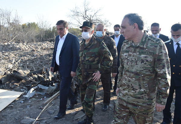 An Azerbaijan senior military officer (right, foreground) inspects a damaged village.