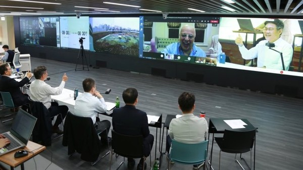 SK E&C CEO Ahn Jae-hyun, right on screen, gestures during an online meeting with Veea CEO Allen Salmasi, left on screen, to sign an MOU for the bilateral partnership on Oct. 21./ Courtesy of SK E&C