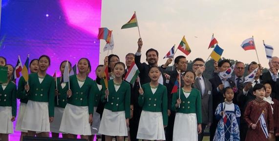 CDA Ossio Bustillos (seventh from right, rear row) waves the flag of his country with other ambassadors and children at a cultural function.