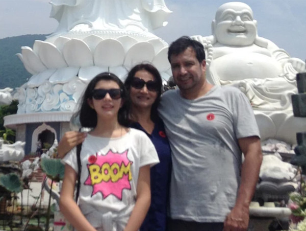 CDA and Mrs. Ossio Bustillos with their daughter, Miss Raquel Otero, in front of the image of Buddhist sculptural works.