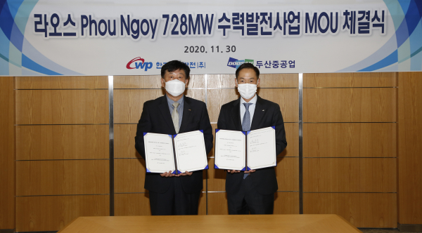 Song Jae-sup (left), head of the planning management division of Korea Western Power, and Park In-won, head of Plant EPC BG of Doosan Heavy Industries & Construction, are taking a commemorative photo after signing the MOU for the Laos hydroelectric project held at Doosan Heavy Industries' Seoul office on Nov. 30/ Courtesy of Doosan Heavy Industries