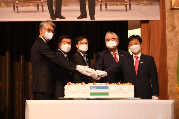 Ambassador Fen (fourth from left) cuts the celebration cake with guests.