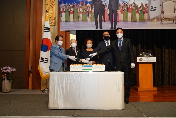 Mrs. Lyumilla Fen (spouse of the ambassador of Uzbekistan), center, cuts the celebration cake with another group of important guests.  Ambassador Ramzi Teymurov of Azerbaijan is seen fourth from left, representing the Seoul Diplomatic Corps.